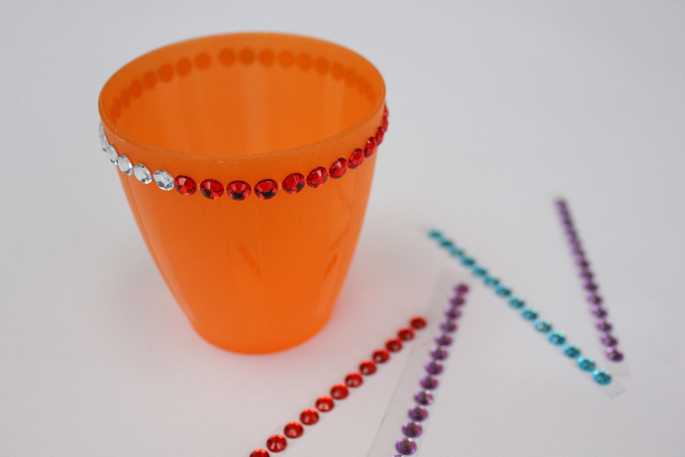 Stick on jewels around the top and the bottom of the cup.