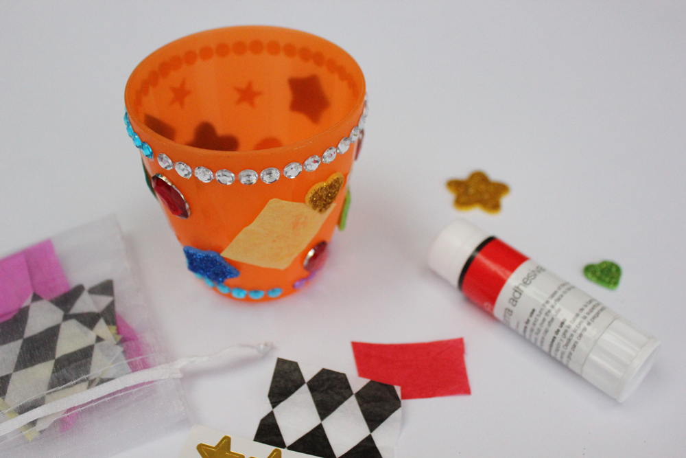 Decorate your cup using glue and paper squares, stars, and gems.