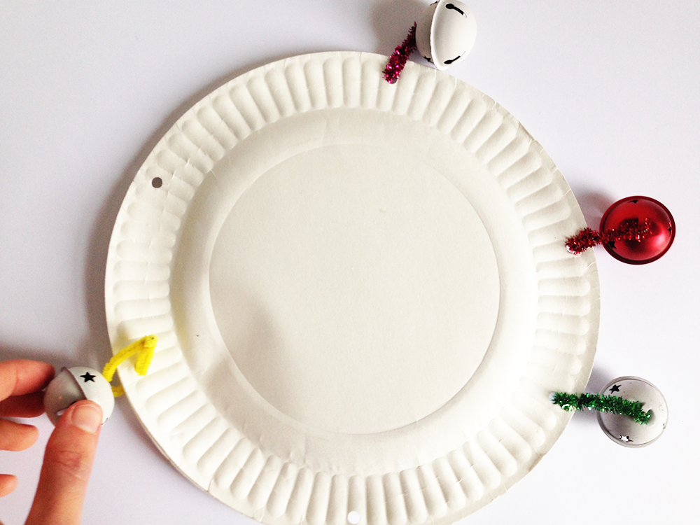 Thread a pipe cleaner through a bell and attach it to the plate using one of the holes. Do this for each of the 6 bells.