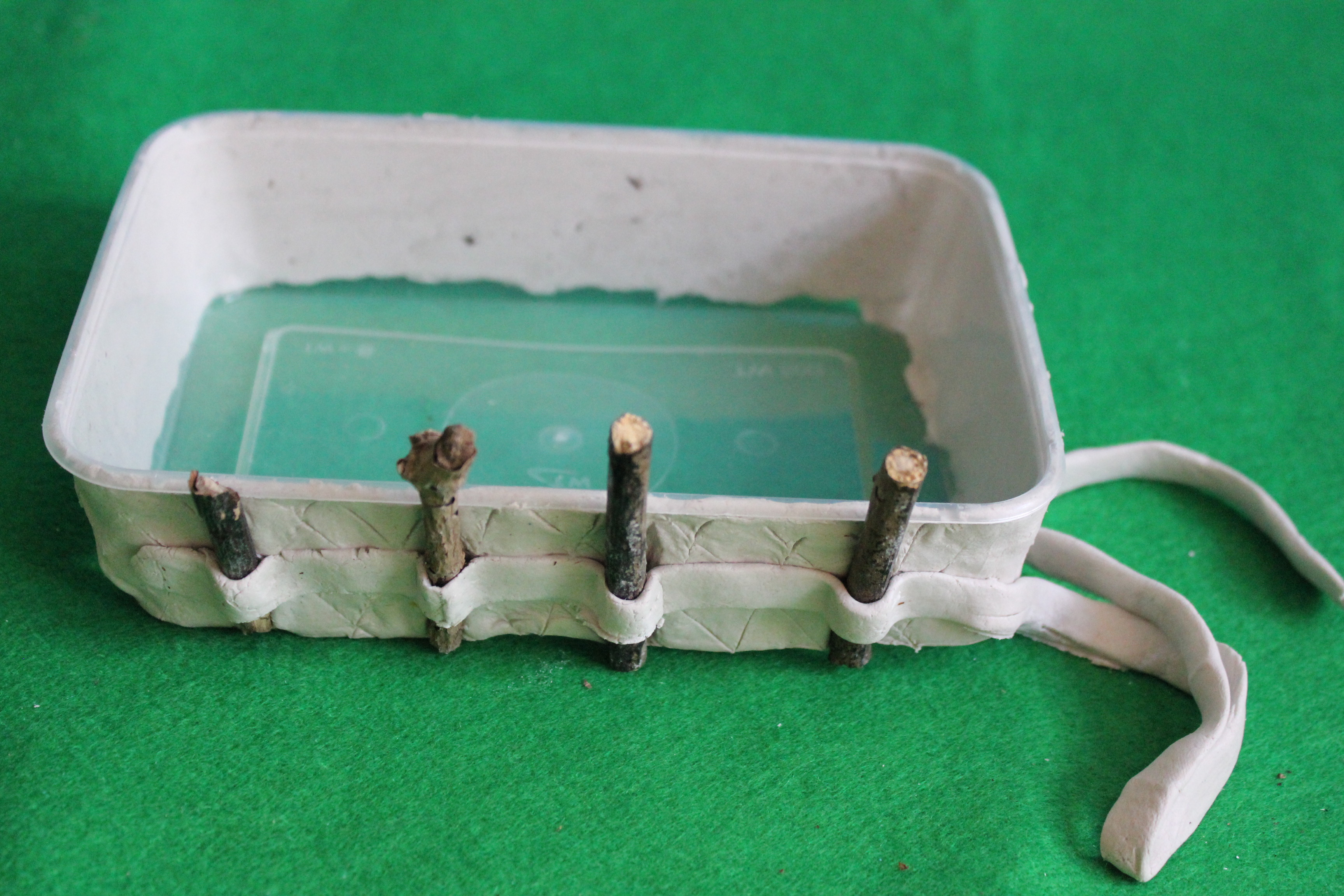 Wrap the clay over the twigs, around the box. Make sure to press very firmly to make the clay and twigs stick together properly. The clay will dry solid within 2 days.