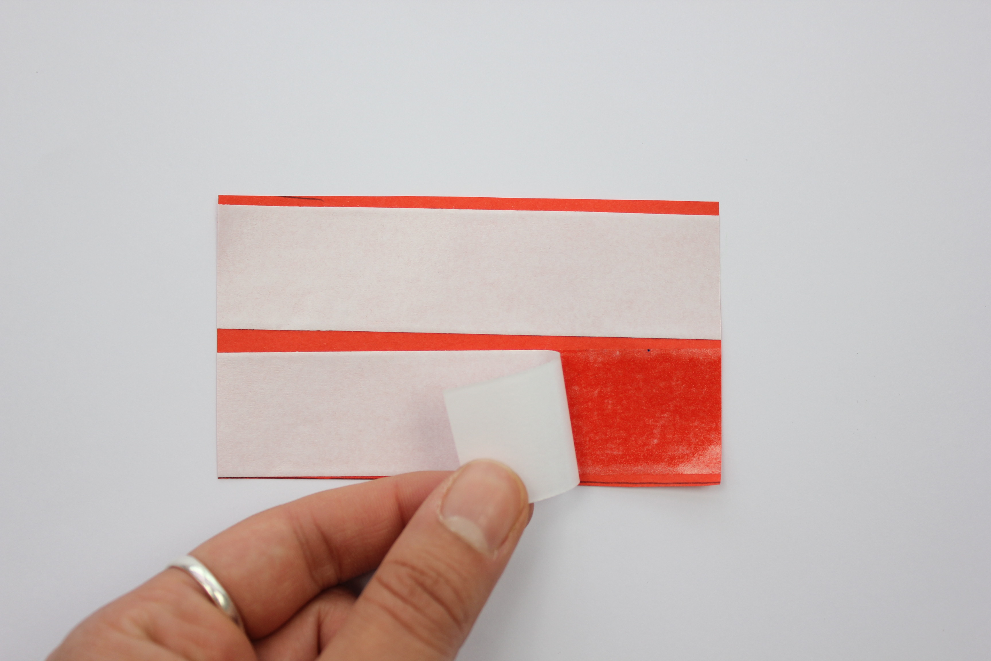 Peel off the white backing of the double sided tape on the red paper.