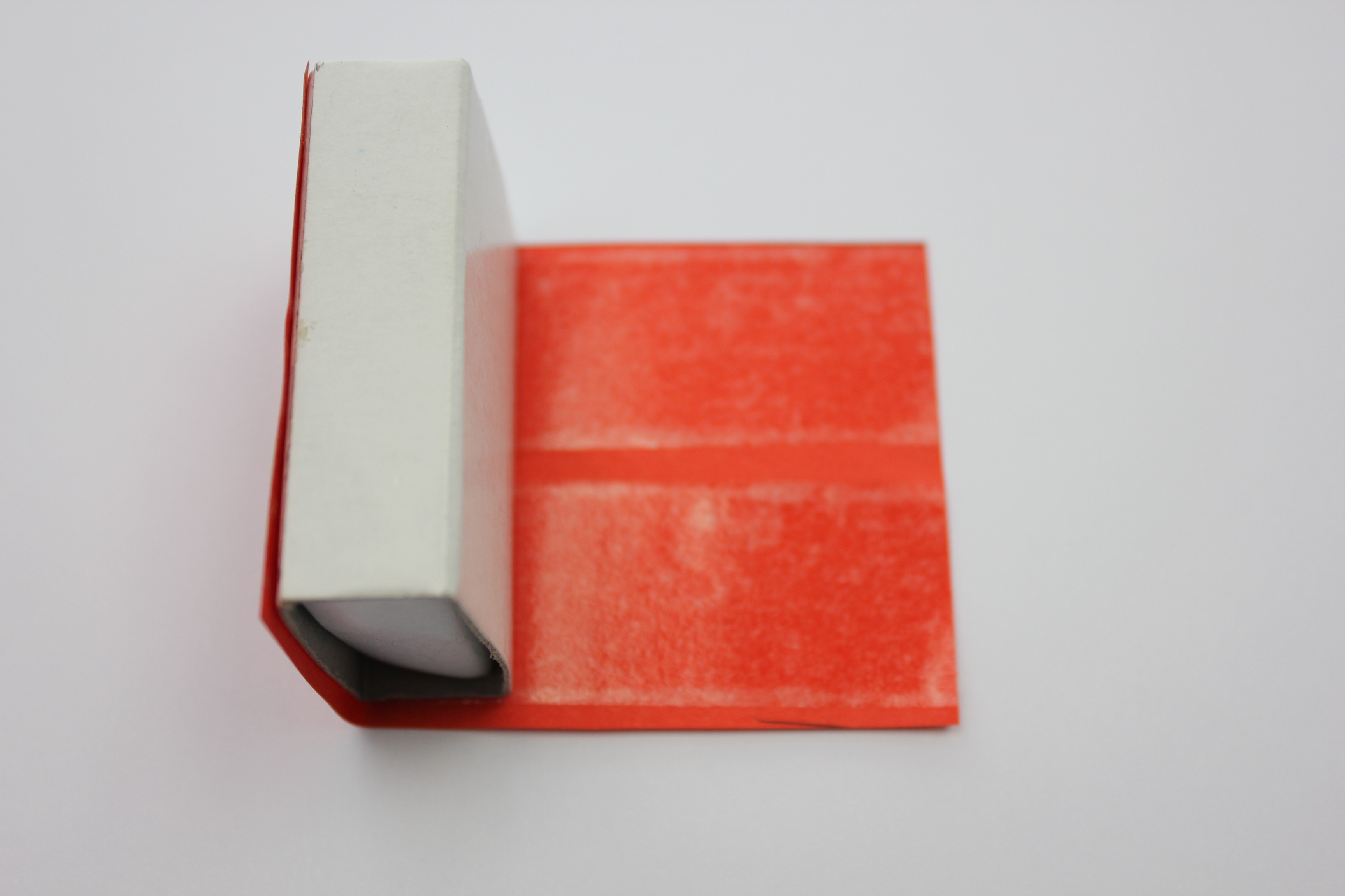 Align the red paper on the white box and stick it on, rolling it around the box covering all but the two smallest sides.