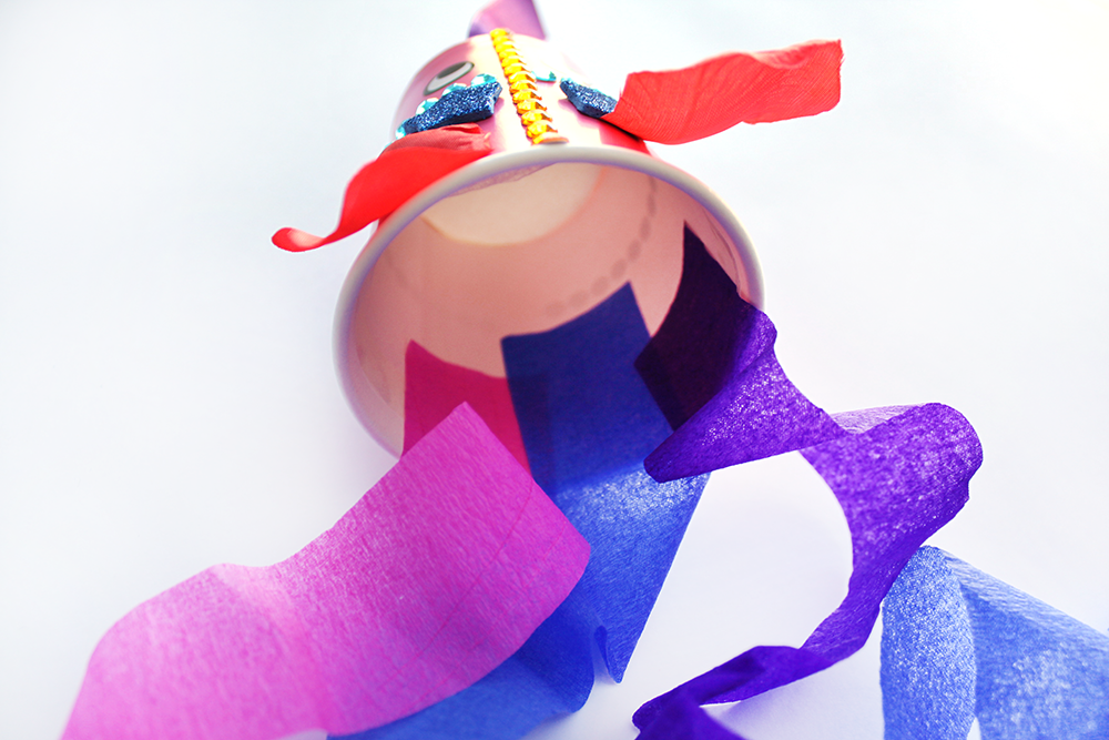 3. Line the inside of the cup with double sided tape and attach the coloured paper to create the tail.
